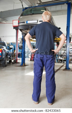Rear view of mechanic looking at car in auto repair shop with hands on waist - stock photo