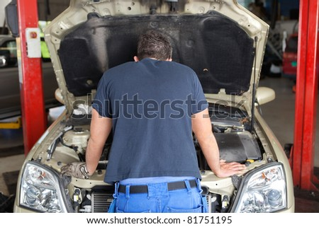 Rear view of mechanic working on a car in garage - stock photo