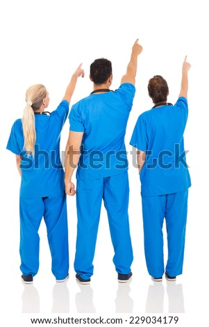 rear view of medical doctors pointing empty space - stock photo