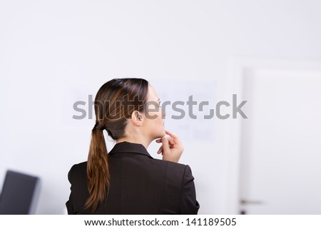 Rear view of mid adult businesswoman thinking with hand on chin in office - stock photo