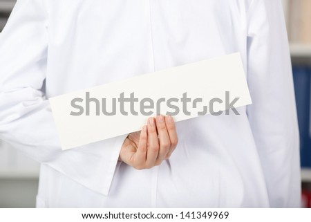 Rear view of mid adult female doctor holding blank label in clinic - stock photo