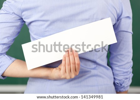 Rear view of mid adult female teacher holding blank label in class - stock photo