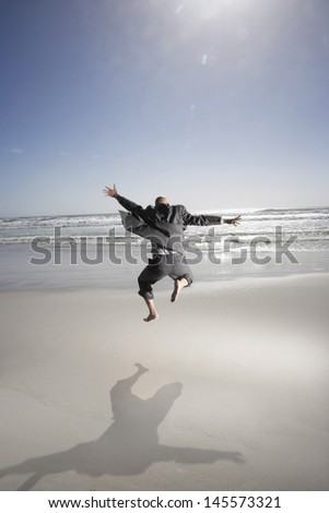 Rear view of middle aged businessman jumping on beach - stock photo