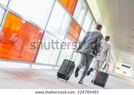 Rear view of middle aged businessmen with luggage rushing on railroad platform - stock photo