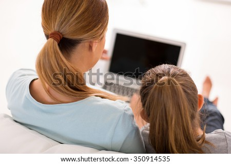 rear view of mother and little daughter using laptop in living room - stock photo