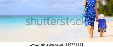 rear view of mother and little daughter walking on tropical beach, panorama