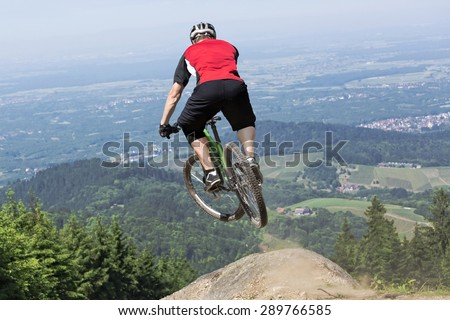 Rear view of mountain bike rider who jumps over a dirt track kicker. The chosen perspective gives the impression of a jump into the precipice. The background shows the black forest in germany. - stock photo