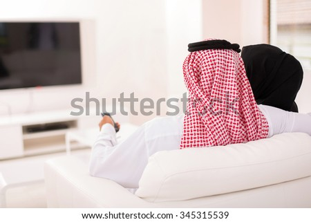 rear view of muslim couple watching tv at home - stock photo