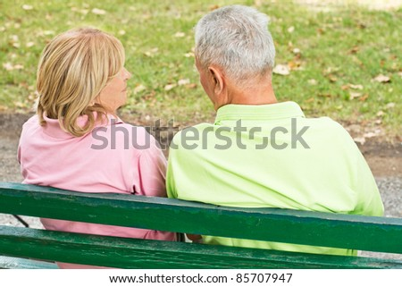 Rear view of old couple sitting and talking on park bench.