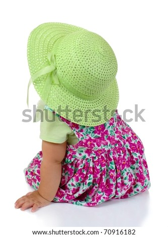 rear view of one year old baby girl toddler looking up leaning on one arm, on white background - stock photo