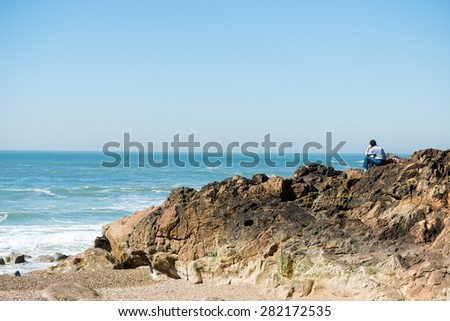 Rear view of pensive, depressed man sitting on coast rock, looking at sea horizon.Copy space, unrecognizable person - stock photo