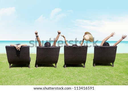 Rear view of people on a deck chair relaxing on the beach - stock photo