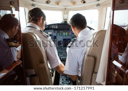 Rear view of pilot and copilot in cockpit of corporate jet - stock photo