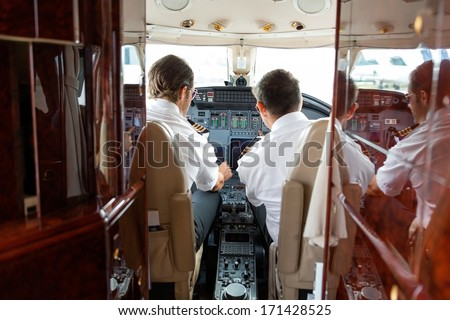 Rear view of pilot and copilot operating controls of private jet - stock photo