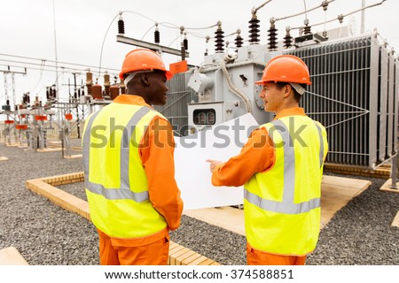 rear view of power company electrician working together in electrical substation - stock photo