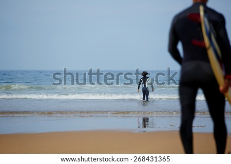 Rear view of professional male surfers carrying their surfboards going to the sea, two surfer guys going to the ocean ready for surf session at perfect sunny day  - stock photo