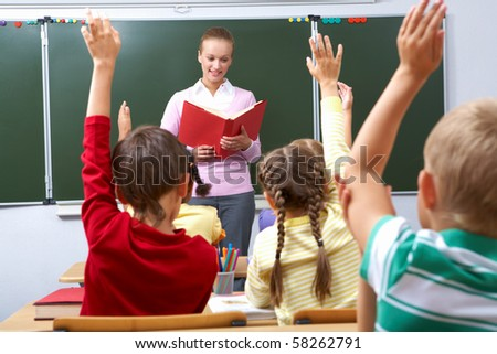 Rear view of pupils raising arms during the lesson with teacher looking at them - stock photo