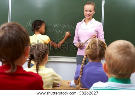 Rear view of pupils sitting at the lesson and looking at teacher while girl writing on blackboard