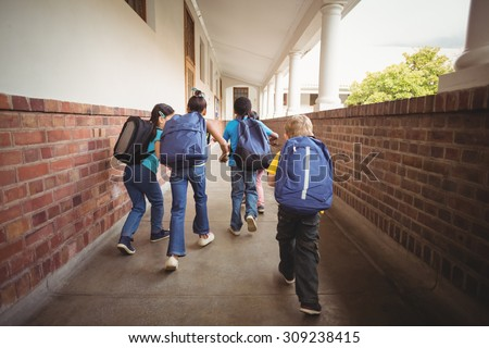 Rear view of pupils walking at corridor in school - stock photo