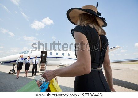 Rear view of rich woman with shopping bags walking towards private jet while pilot and stewardesses standing at airport terminal - stock photo