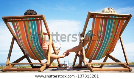 Rear view of romantic couple relaxing on beach chairs - stock photo