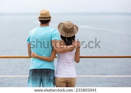 rear view of romantic young couple looking at the sea from cruise ship - stock photo