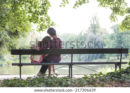 Rear view of romantic young couple sitting on bench at lakeside - stock photo