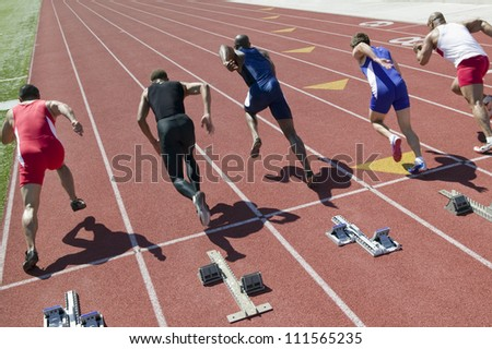 Rear view of runners starting race on racetrack - stock photo