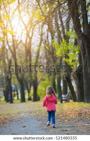 Rear view of running little girl in autumn park.Lens flare