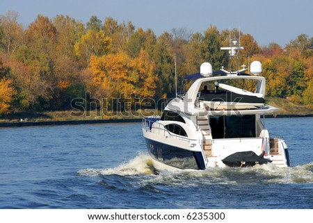 Rear view of sailing luxury yacht on golden autumn scenic background. - stock photo