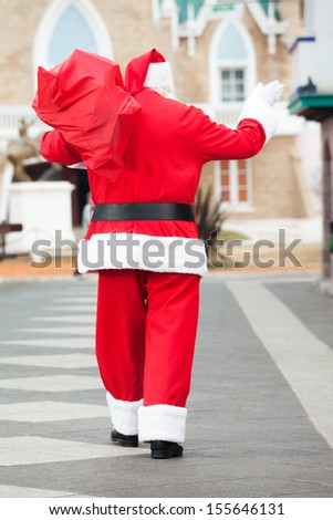 Rear view of Santa Claus with bag waving while walking in courtyard - stock photo