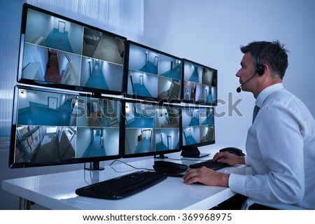Rear view of security system operator looking at CCTV footage at desk in office
