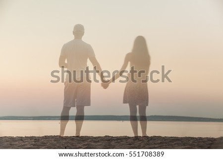 Rear view of semi-transparent man and woman in summer dress on beach looking at sea on sunset.