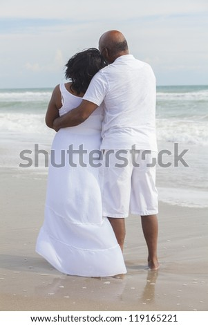 Rear view of senior African American man and woman couple on a deserted tropical beach - stock photo