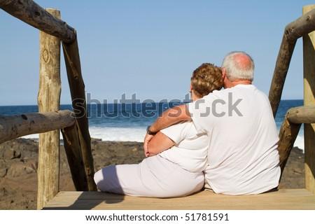 rear view of senior couple cuddling on beach - stock photo