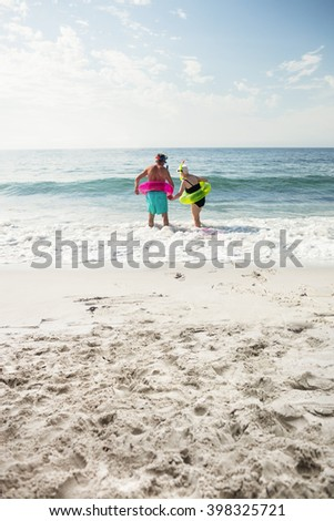 Rear view of senior couple enjoying on beach on a sunny day - stock photo