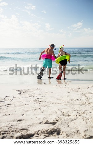 Rear view of senior couple in inflatable ring and flipper walking towards sea on a sunny day - stock photo