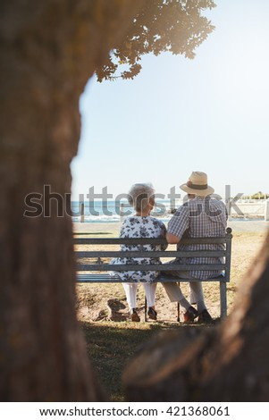 Rear view of senior couple sitting on bench near the sea. Elderly man and woman relaxing on a bench looking out to sea. - stock photo