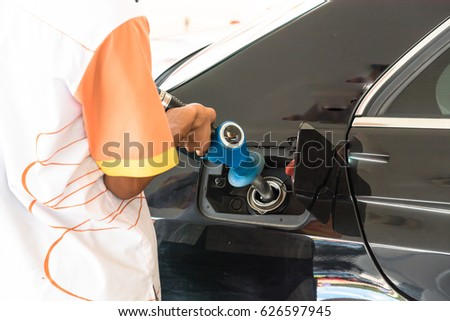 Rear view of service station worker pumping gas in to the tank of modern car. Close-up male hand holding gas nozzle refilling fuel, man pumping gasoline at gas station in Malaysia.