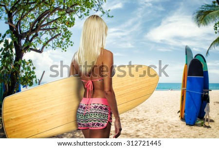 Rear view of sexy beautiful young woman surfer girl in bikini with white surfboard at a beach in Bali indonesia - stock photo