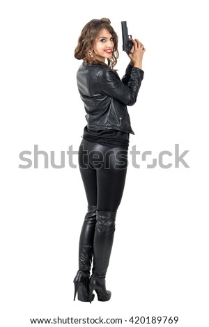 Rear view of sexy dangerous woman holding a gun turn head and smiling at camera. Full body length portrait isolated over white studio background.  - stock photo