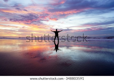 Rear view of Silhouette a man raising His Hands appreciating beautiful landscape. - stock photo