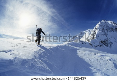 Rear view of skier hiking to mountain summit - stock photo