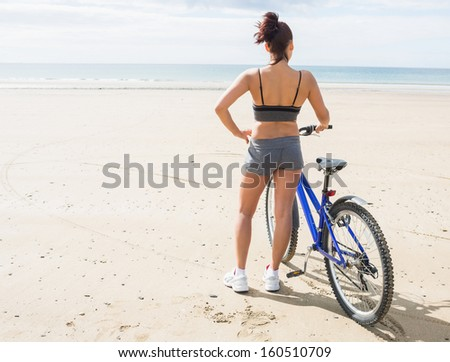 Rear view of slender young woman standing on the beach with her bike - stock photo
