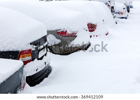 rear view of snow covered cars in parking lot