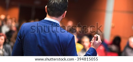Rear view of speaker giving a talk on corporate Business Conference. Audience at the conference hall. Business and Entrepreneurship event. Panoramic composition. - stock photo