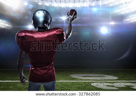 Rear view of sportsman in red jersey holding ball against american football arena - stock photo