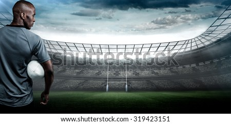Rear view of sportsman with rugby ball against rugby stadium - stock photo