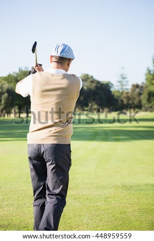 Rear view of sportswoman playing golf on field - stock photo