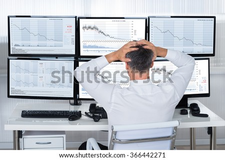 Rear view of stock trader with hands on head looking at graphs on screens